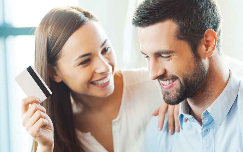 Couple smiling with credit card.