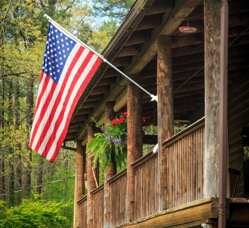 American flag flying from the front porch of a log cabin home